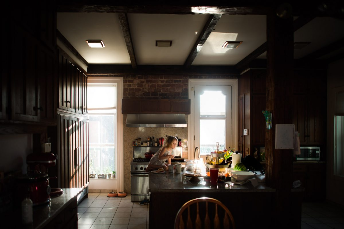Beautiful-Messy-Everyday-Photo-of-Little-Girl-Climbing-on-Kitchen-Counter-With-Beautiful-Reflected-Natural-Light-by-Sarah-Wilkerson-1624