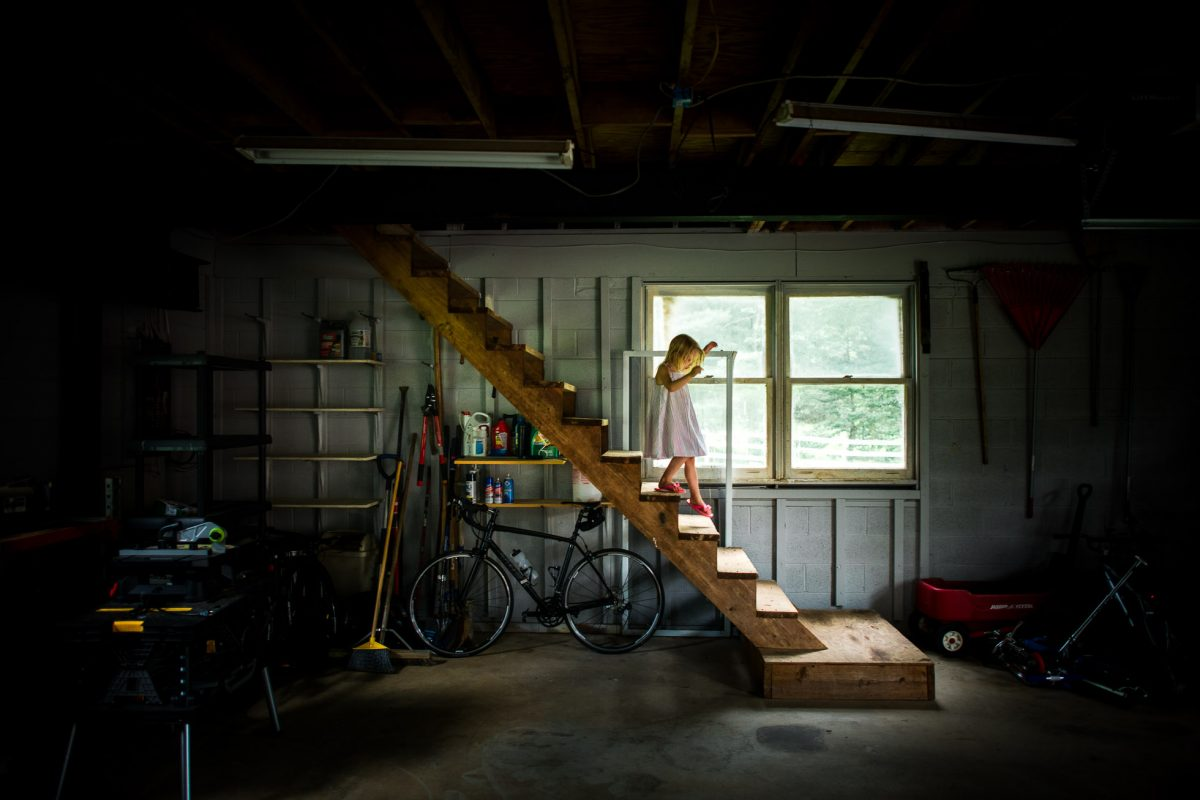 Colorful-Everyday-Documentary-Photo-with-Lines-and-Shapes-of-Little-Girl-Balancing-in-Light-Pocket-on-Stairs-in-Old-Garage-5492