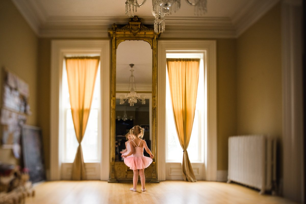Environmental-Tilt-Shift-Natural-Light-Portrait-with-Symmetrical-Composition-of-Tiny-Ballerina-Standing-in-front-of-Reflection-of-Giant-Mirror-by-Photographer-Sarah-Wilkerson-